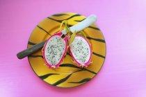 Fruta de dragón a la mitad en plato - foto de stock