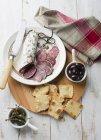 Salami, galletas y alcaparras - foto de stock