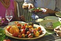 Gente que come tomates en una mesa de jardín en el verano, abdomen - foto de stock