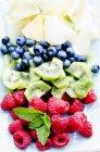 Frische geschnittene Früchte mit Minzblättern — Stockfoto