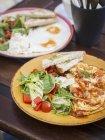 Vista del primo piano di crepes con insalata, uova fritte e pane tostato — Foto stock