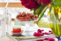 Vista de closeup de morangos frescos em copo prato e mocha no livro com pétalas de rosa — Fotografia de Stock