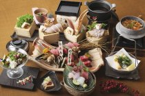 Elevated view of platters with salad, sashimi and mussel tempura — Stock Photo