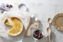 Crme brle tart with dates over white surface with chopping board — Stock Photo