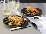 Chicken in white wine sauce and asparagus on black plates on table — Stock Photo