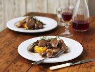 Coq au vin servita sulla zucca di butternut puro con timo ed erba cipollina sulle zolle bianche sulla superficie di legno — Foto stock