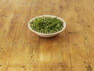 Zutaten für Erbsen- und Minzsuppe auf weißem Teller über Holzoberfläche — Stockfoto