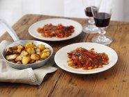 Piri-piri pollo con patate arrosto e vino sulle zolle bianche su superficie di legno — Foto stock