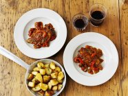 Piri-piri chicken with roast potaotes and wine (seen from above) — Foto stock