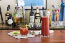 Классический напиток Кровавой Мэри с сельдереем на столе с домашним баром на заднем плане — стоковое фото