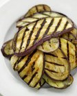 Grilled aubergine slices on white plate — Stock Photo