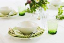 Крупный план установки места с тарелками для супа и цветочным декором — стоковое фото