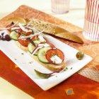 Зерно багет, увінчаний грецький салат на білий плита — стокове фото