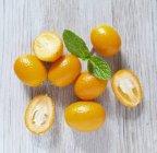 Kumquat freschi maturi con metà — Foto stock