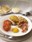 Colazione all'inglese con uova fritte, pancetta e fagioli cotti sulla zolla bianca — Foto stock