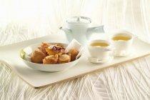 Churros and tea on the tray — Stock Photo