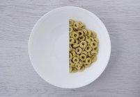 Porción reducida a la mitad de aros de cereales - foto de stock