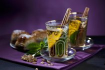 Tea Eastern-style with mint, cinnamon, orange and baklava over purple surface — Stock Photo