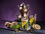 Closeup view of Eastern-style tea with mint, cinnamon, orange and baklava — Stock Photo