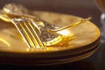Крупним планом зору Золотий вилки на stacked золотими пластинами — стокове фото