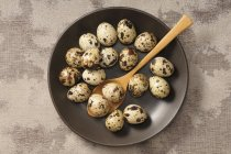 Quail eggs in bowl with wooden spoon — Stock Photo