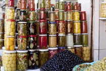 Lots of jars of assorted preserved food and mounds of olives in a shop — Stock Photo