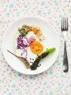 Draufsicht auf einen Salatteller mit Tomaten, Rotkraut, essbaren Sprossen und schwarzen Linsen — Stockfoto