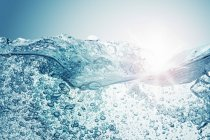 Closeup view of moving water surface with air bubbles — Stock Photo