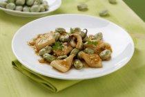 Tintenfisch mit Bohnen auf weißen Teller über grünen Handtuch — Stockfoto