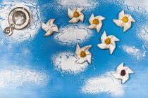 Top view of puff pastry pinwheels with icing sugar on blue surface — Stock Photo