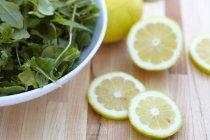 Аругула и нарезанный лимон — стоковое фото