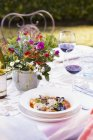 Outdoor table with mixed shellfish in tomato broth with herbs — Stock Photo