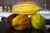 Vista del primo piano di quattro baccelli del cacao su superficie riflettente scuro — Foto stock