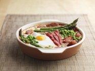 Gebackenen Eiern Paprika Spargel Erbsen und Chorizo in Platte über Textiloberfläche — Stockfoto