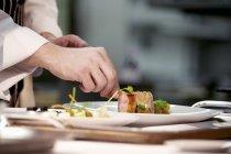 Chef plating up pork — Stock Photo