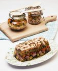 Turkey aspic with vegetables and peas on white surface and chopping board over table — Stock Photo