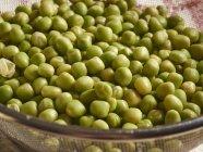 Пропитанный зеленым горошком в сито — стоковое фото