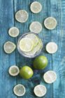Glass of water with fresh limes — Stock Photo