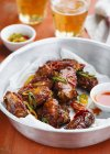 Chicken wings with chilli sauce and beer in dish over table — Stock Photo