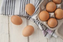 Brown eggs in egg box with fabric — Stock Photo