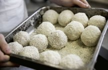 Closeup view of a chef holding a baking tray of Arancini — Stock Photo