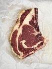 Сырой говяжий стейк на бумаге — стоковое фото