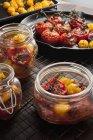 Pomodori rossi e gialli arrostiti in barattoli e in padella — Foto stock