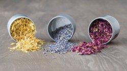 Сушеная Мэриголд, лаванда и лепестки роз в перевернутых банках — стоковое фото