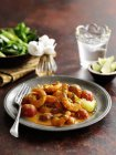 Southern Indian prawn curry on black plate with fork — Stock Photo