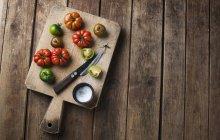 Tomates diverses sur une planche à découper avec du sel et un couteau sur la surface de woden — Photo de stock