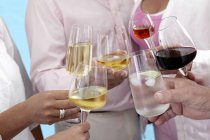 Closeup view of people toasting with glasses of different drinks — Stock Photo