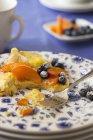 Tortilla dulce con arándanos, duraznos y azúcar glas, parcialmente comido - foto de stock