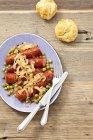 Salsiccia con cipolle su piastra — Foto stock