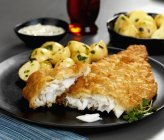 Battered plaice with herb potatoes and tartar sauce on black plate — Stock Photo